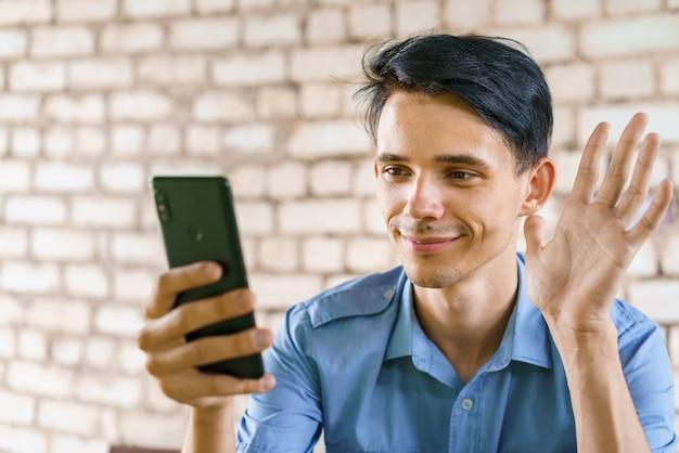 젊은 남자는 전화를 통해 비디오 통신으로 통신합니다. 파란색 셔츠를 입은 남자