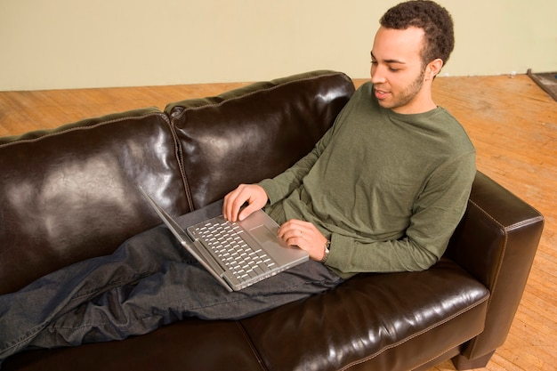Young man computing on couch