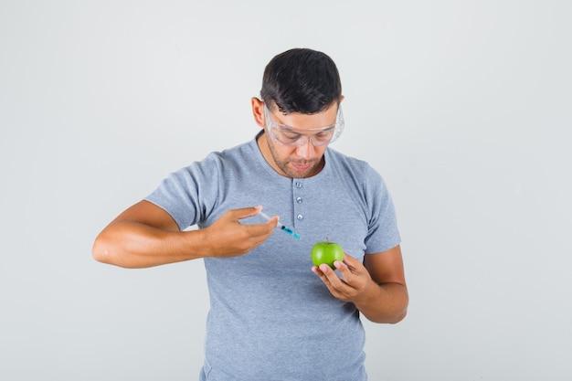 若い男が灰色のtシャツでリンゴに注射によって実験を実施