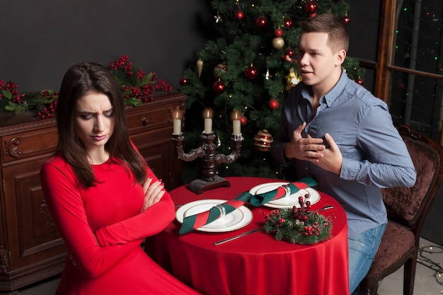 Young man confesses his love for dissatisfied beautiful woman, love couple at luxury restaurant.