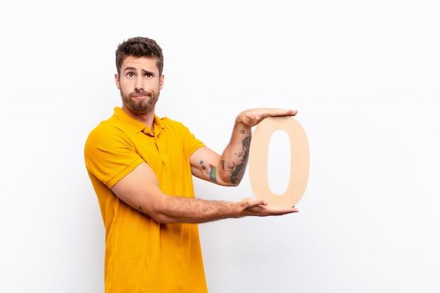 Молодой человек смущен, держа номер 0