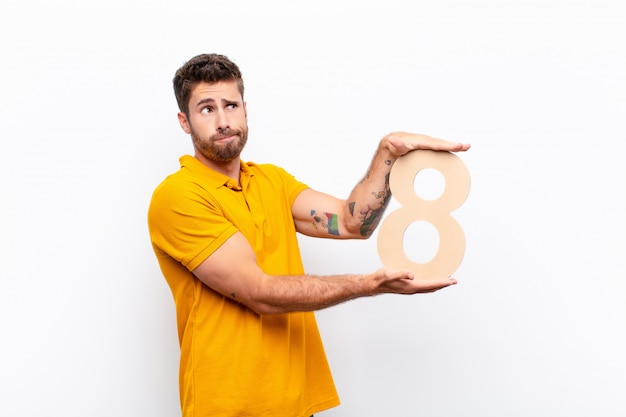 Young man confused holding a number 8