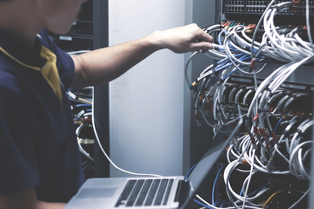 Young man connecting wires in server cabinet while working with laptop in data center
