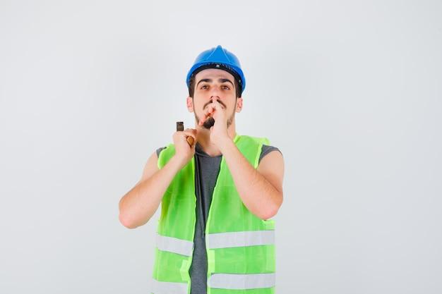 Giovane in uniforme da costruzione che alza l'ascia sopra la spalla e mostra il gesto del silenzio e sembra concentrato