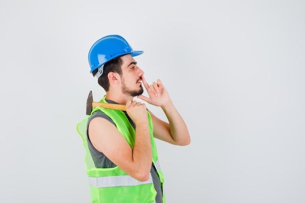 Giovane in uniforme da costruzione che alza il martello sulla spalla e mostra il gesto del silenzio e sembra concentrato