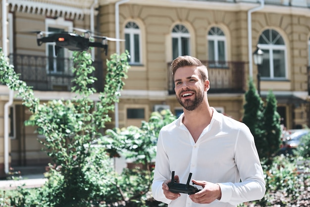 Young man control drone while sitting at pier in old european city