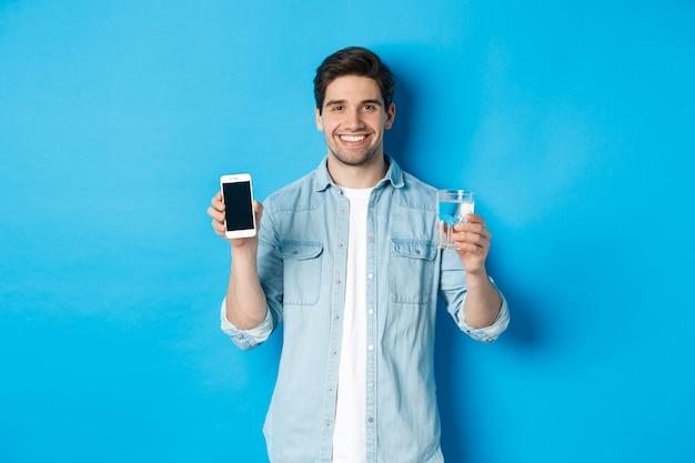 Il giovane controlla il bilancio idrico con l'app per smartphone, mostrando l'app sullo schermo mobile e sorridendo, in piedi su sfondo blu
