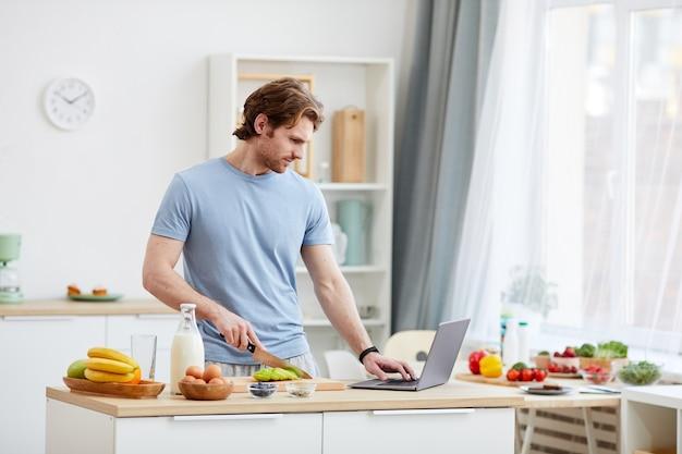 Молодой человек сам готовит завтрак и смотрит онлайн-курс на портативном компьютере на кухне