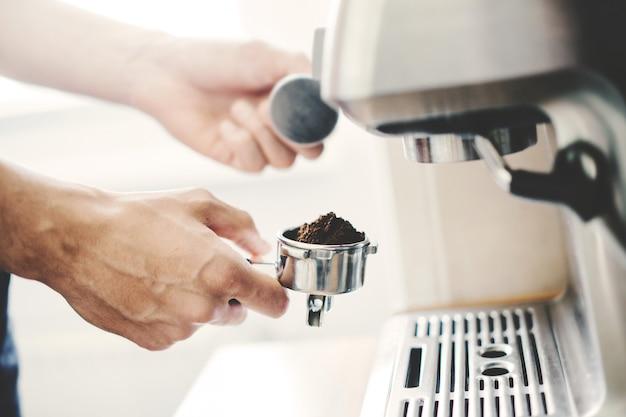 자동 coffeemachine 집에서 커피를 요리하는 젊은 남자.