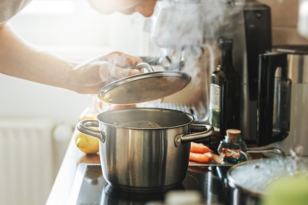 Young man cooking fresh food at home and opening lid of steaming pot.