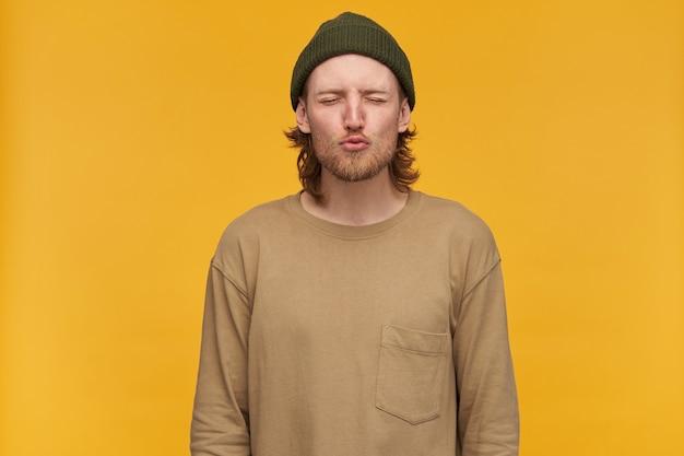 Giovane, simpatico ragazzo con capelli biondi, barba e baffi. indossare berretto verde e maglione beige. increspa le labbra in un bacio e tiene gli occhi chiusi. stare isolato su una parete gialla