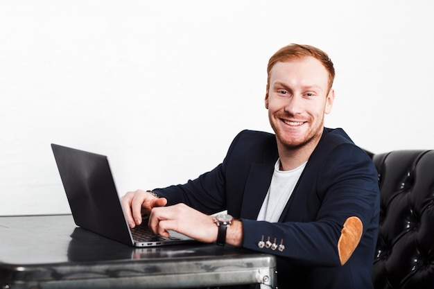 Young man copywriter in a suit typing on laptop and smiling