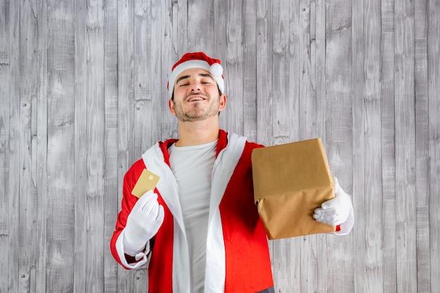 クレジットカードとギフトでサンタクロースの衣装を着た若い男