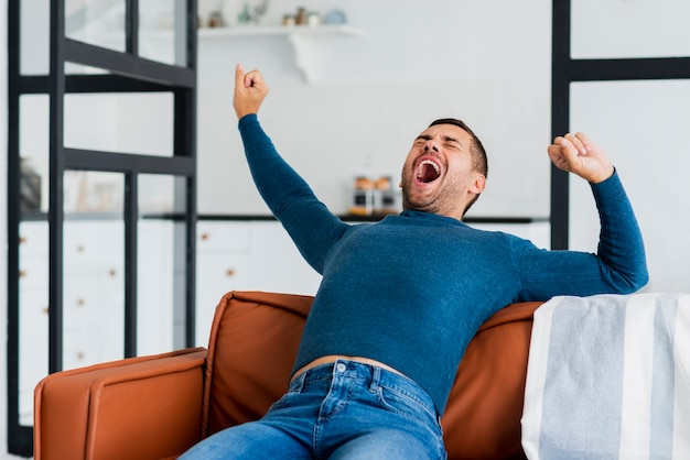 Young man on couch yawning