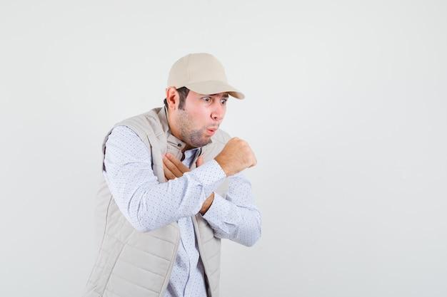 Молодой человек кашляет в рубашке, куртке без рукавов, кепке и выглядит больным, вид спереди.