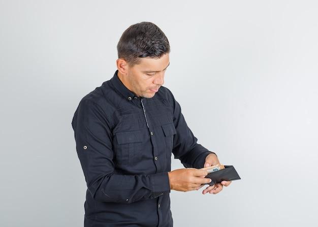 Молодой человек считает деньги в бумажнике в черной рубашке