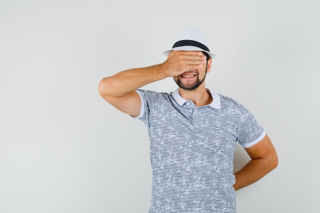 Young man covering eyes with hand in t-shirt, hat and looking excited , front view.