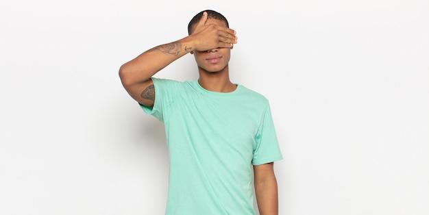 片手で目を覆っている青年が怖い、不安、不思議、または盲目的に驚きを待っている