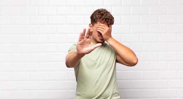 Молодой человек закрывает лицо рукой и поднимает другую руку вперед, чтобы остановить камеру, отказываясь от фотографий или изображений