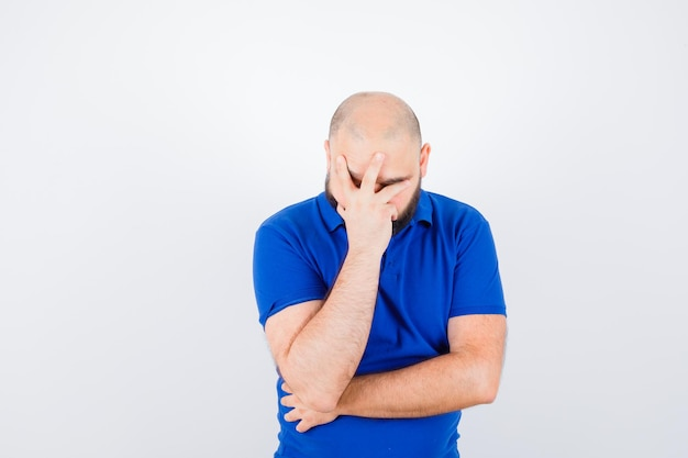 Giovane che copre il viso con la mano in camicia blu e sembra sconvolto. vista frontale.