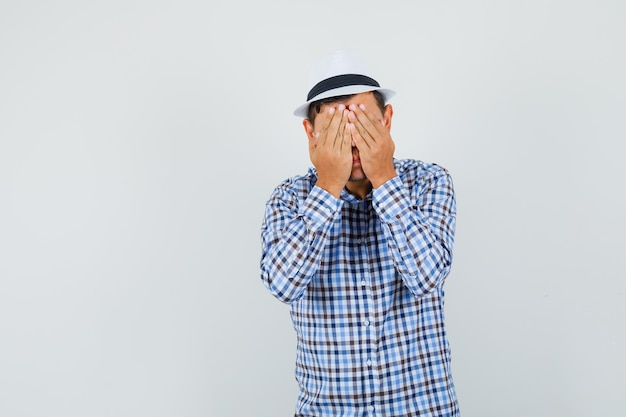 Young man covering face with hands in checked shirt