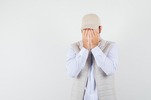 젊은 남자 셔츠, 민소매 재킷, 모자에 손으로 얼굴을 덮고 부끄러운, 전면보기를 찾고. 텍스트를위한 공간