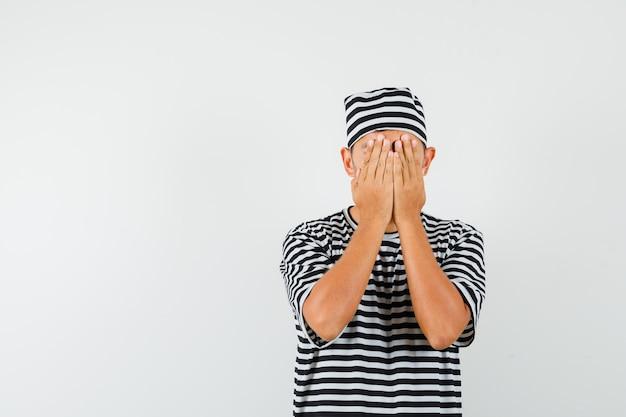 스트라이프 티셔츠 모자에 손으로 얼굴을 덮고 두려워하는 젊은 남자
