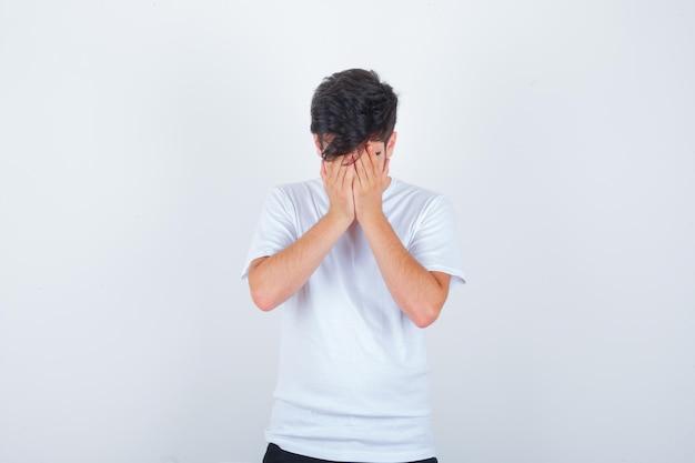 白いtシャツで顔を手で覆い、悲しそうに見える若い男