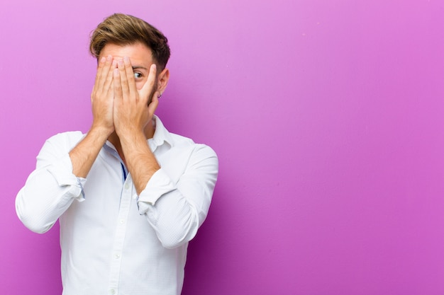 Young man covering face with hands, peeking between fingers with surprised expression and looking to the side against purple wall