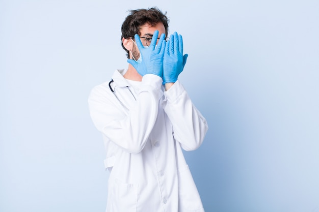 Young man covering face with hands, peeking between fingers with surprised expression and looking to the side. coronavirus concept