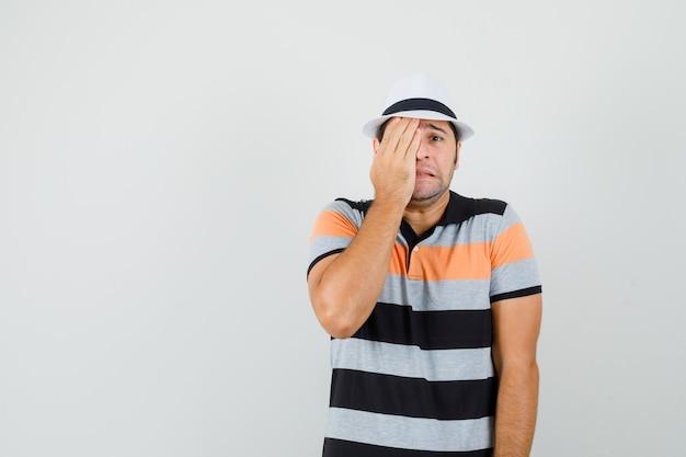 스트라이프 티셔츠, 모자에 그의 손으로 얼굴을 덮고 텍스트에 대한 스트레스가 많은 공간을 찾는 젊은 남자