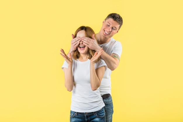 Young man covering her girlfriends eyes with two hands shrugging on yellow backdrop