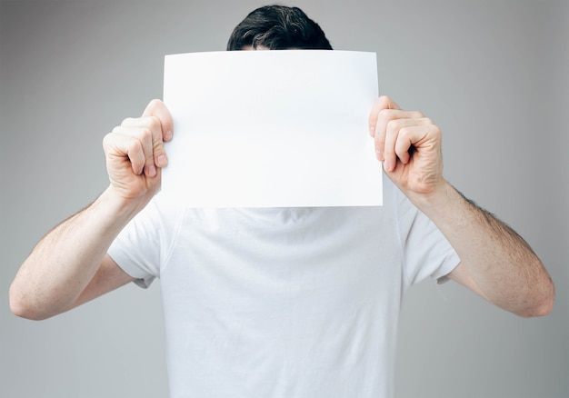Young man covering his face with white blank paper sheet