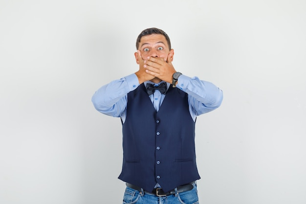 Молодой человек закрывает рот руками в костюме, джинсах и выглядит испуганным