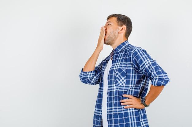 Молодой человек, закрывающий рот рукой в рубашке.