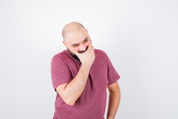 분홍색 티셔츠를 입은 허리에 손을 잡고 생각에 잠긴 앞모습을 바라보면서 손으로 입을 가리고 있는 젊은 남자.