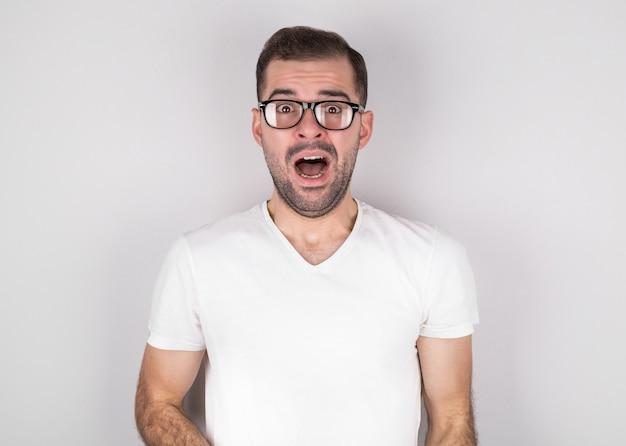 Молодой человек, закрывающий рот руками и круглыми глазами, в круглых очках, испытывает глубокое удивление и страх, изолированный на серой стене