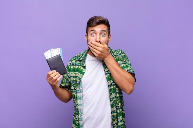 Молодой человек прикрывает рот руками с шокированным, удивленным выражением лица, хранит секрет или говорит: ой. концепция праздников