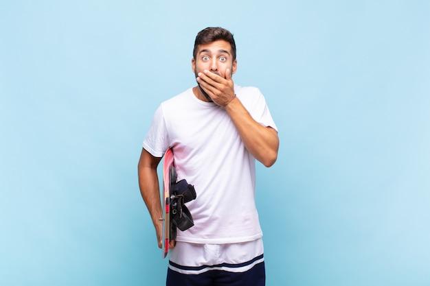 Молодой человек прикрывает рот руками с шокированным, удивленным выражением лица, хранит секрет или говорит: ой