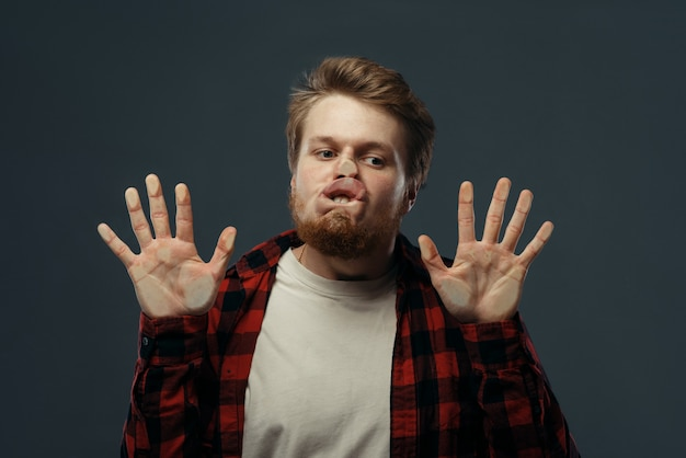 Young man crazy face and hands crushed on transparent glass.