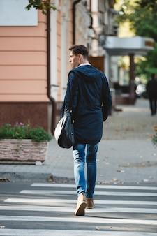 Молодой человек переходит улицу