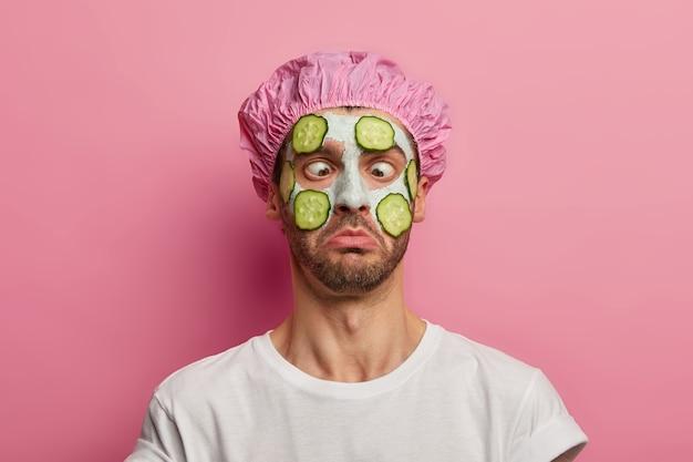 젊은 남자가 눈을 교차하고, 오이로 얼굴에 크림 마스크를 바르고, 미용 세션을 가지고 있으며, 목욕 모자를 쓰고 있습니다.