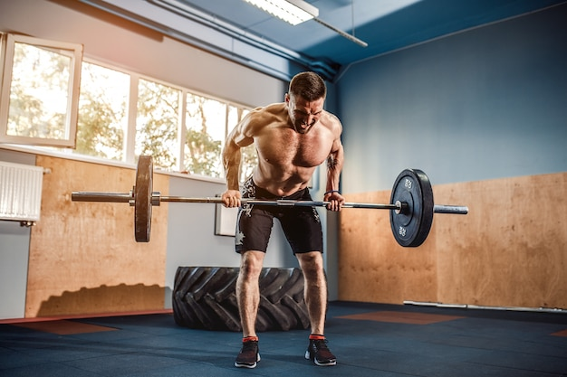 Young man at a crossfit gym lifting a barbell.