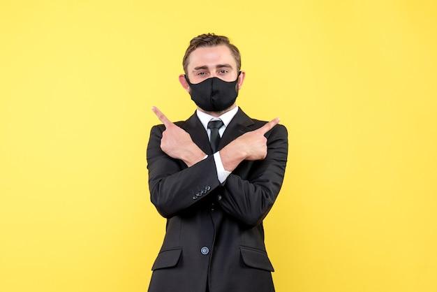 医療マスクで親指を立てながら手を交差する若い男