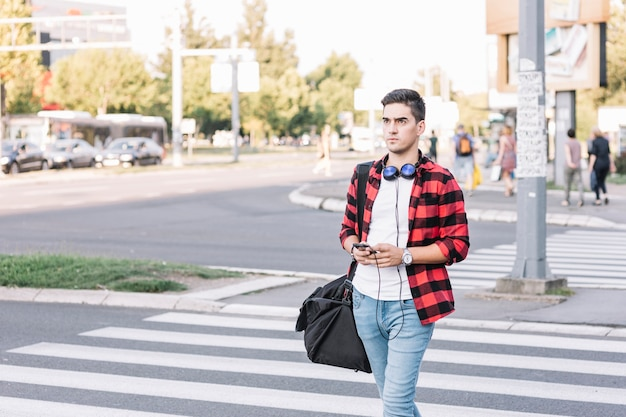 Young man crossing street