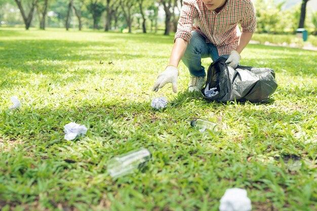 Молодой человек приседает, чтобы тратить и собирает его в мешок для мусора