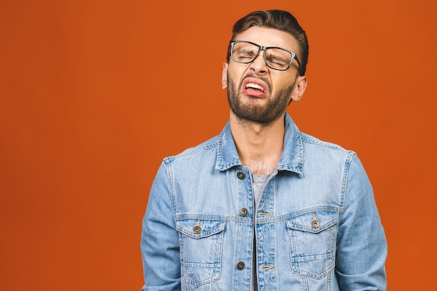Young man crying isolated against orange background