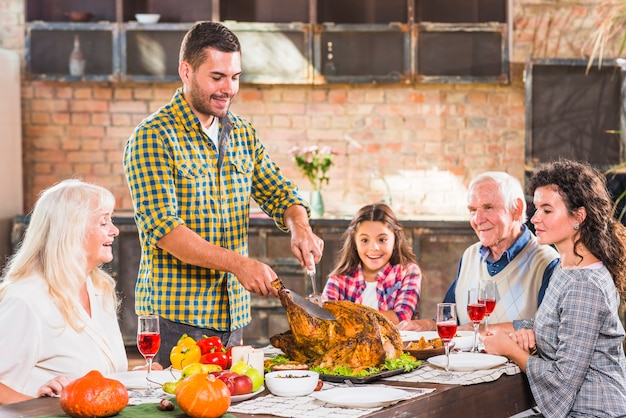 Young man cutting baked chicken at table with family