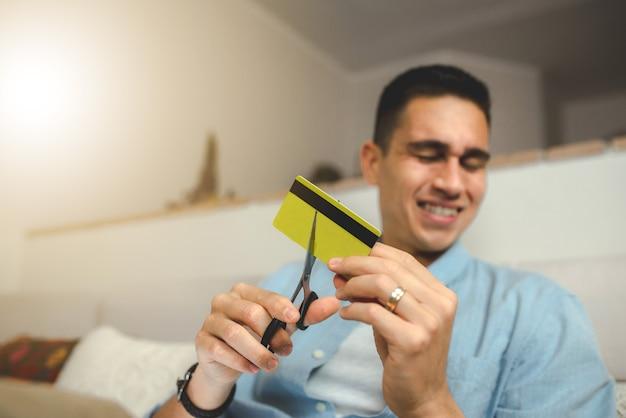 はさみでクレジットカードを切る若い男。ホームバンキングとテクノロジーのコンセプト。