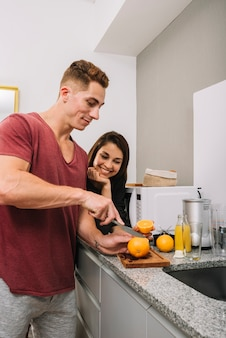 Young man cutting orange in kitchen with woman